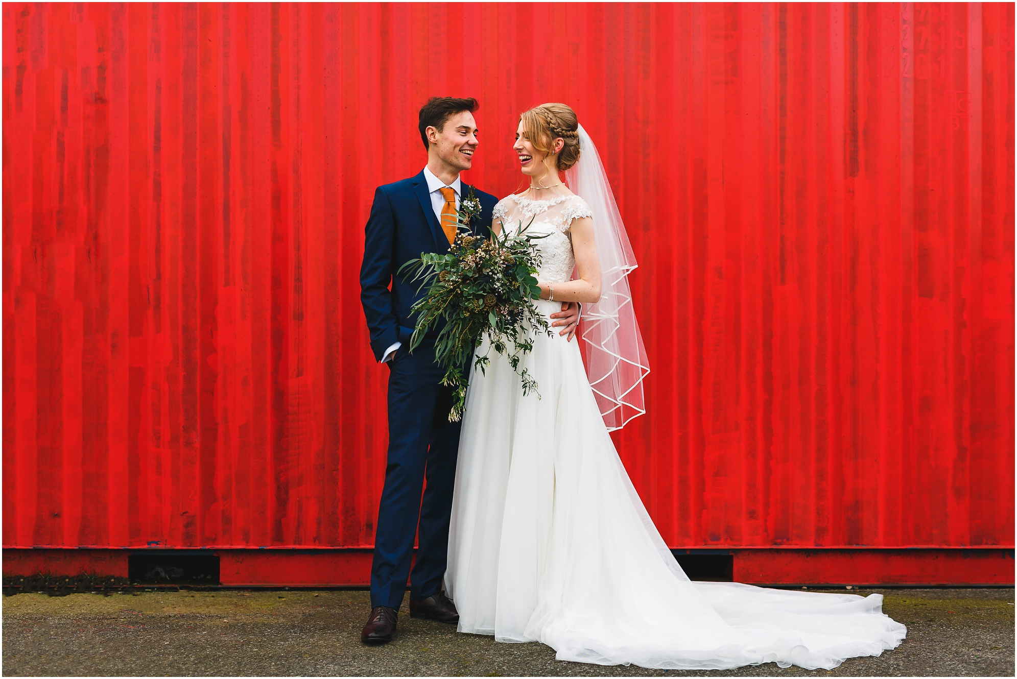 New Mr and Mrs in front of large red rustic background near Donington Park Farmhouse Wedding Photographer Gareth Newstead