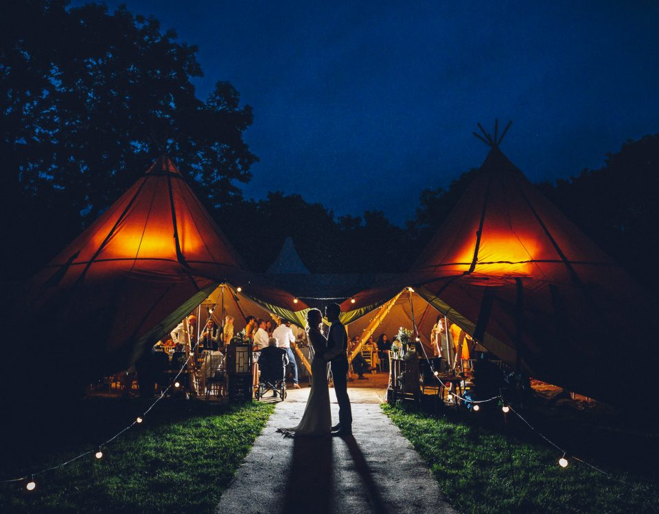 Newlyweds in cool portrait outside tipi at night time