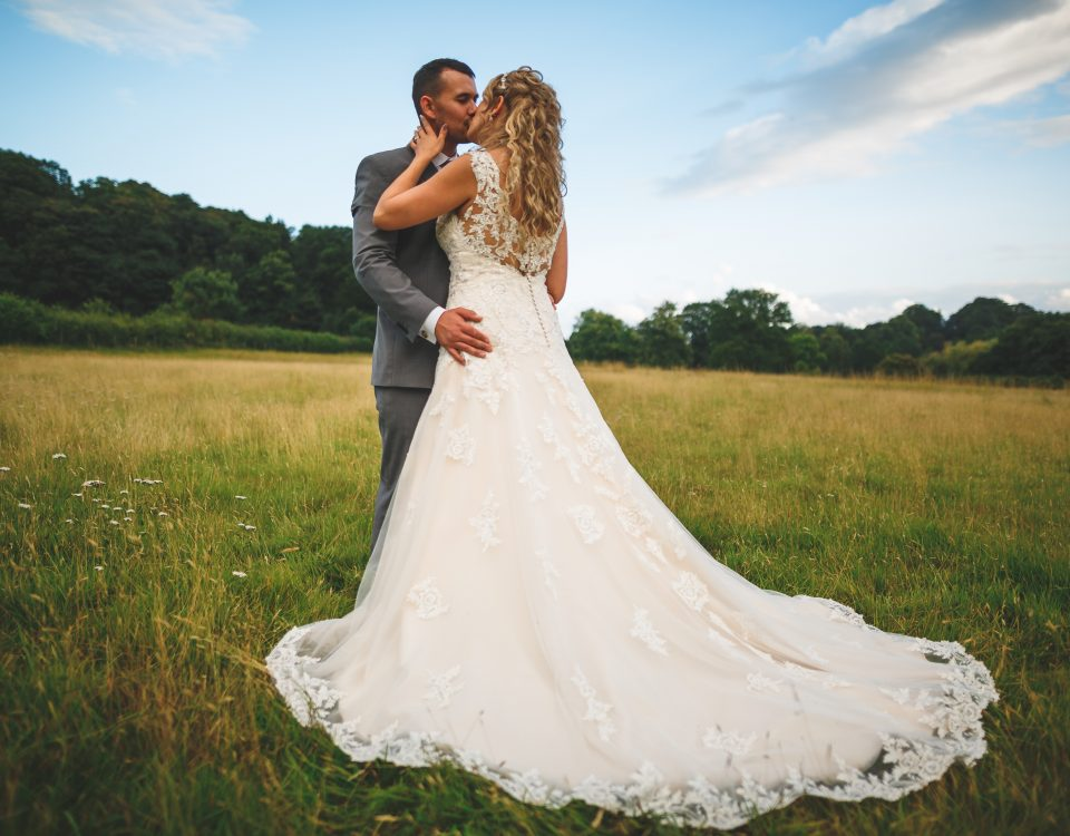 Wedding at Slaters Country Inn, Wedding dress shot with newlywed couple kissing in a field