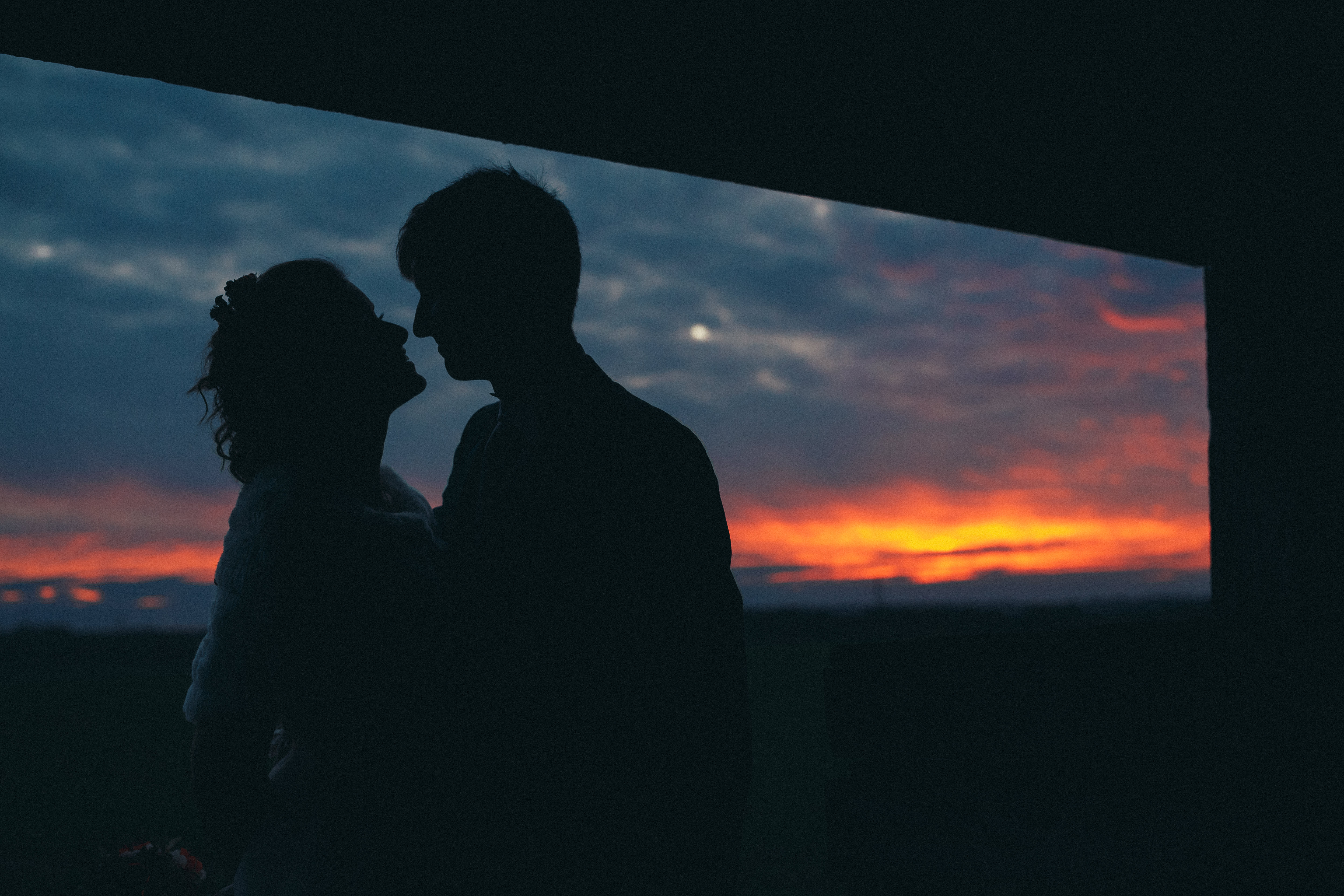 newlyweds silhouette kissing with sunset near barn rustic winter wedding photography
