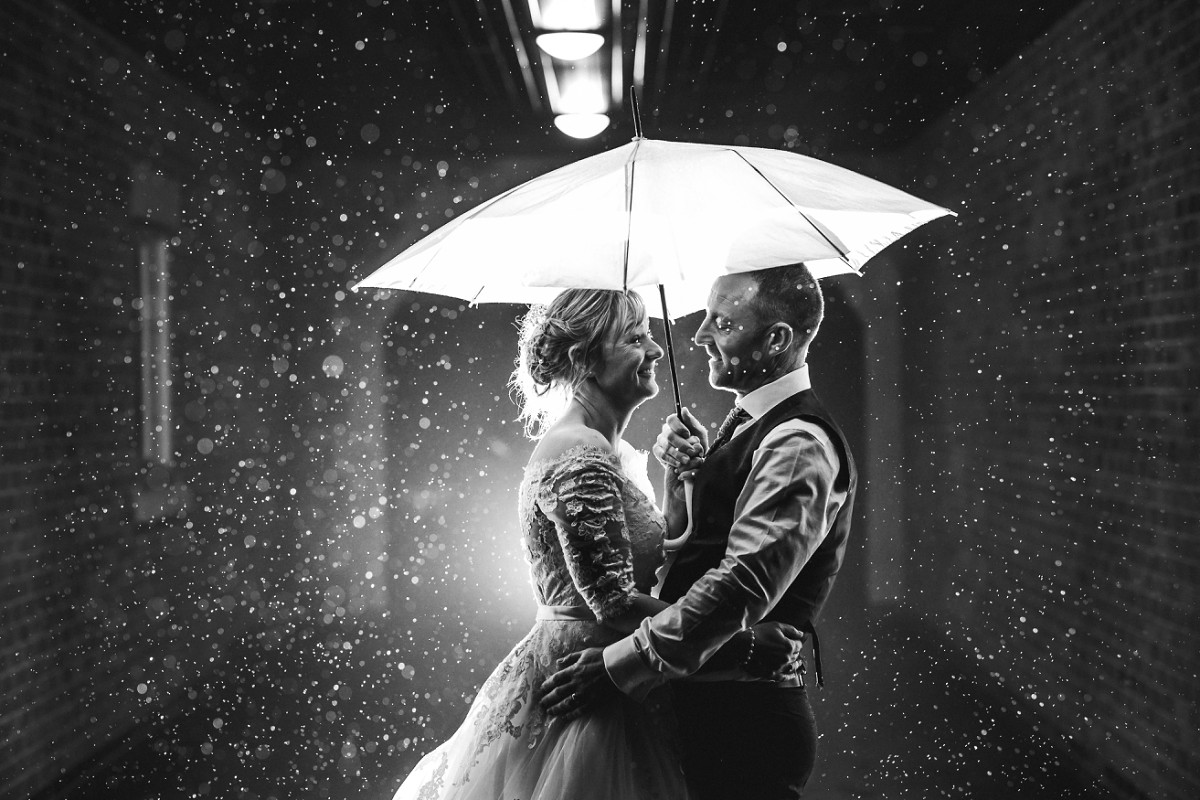 white hart inn wedding photography night portrait shot with couple in the rain under an umbrella